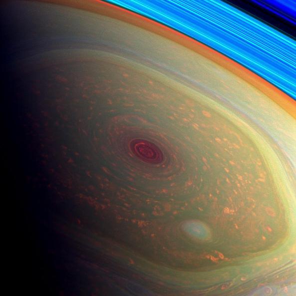 El espectacular vórtice de la tormenta en color rojo oscuro. Justo en el centro del hexágono situado en el polo norte. Las nubes que lo rodean aparecen en color naranja. También observamos otro pequeño vórtice formándose al sur de la imagen.